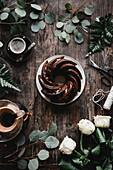 Schokoladenkranzkuchen auf Holztisch umgeben von Blättern und Blumen