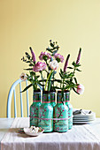 Leere Teeflaschen als Vasen mit Nelken, Ehrenpreis und Eukalyptus