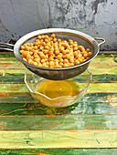 Eingeweichte Kichererbsen in Glasschale abgießen (Aquafaba)