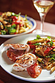 Chicken saltimbocca served with a pasta salad with roasted vegetables