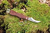 A mushroom knife on mossy ground