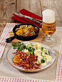 Schnitzel with bacon and fried potatoes