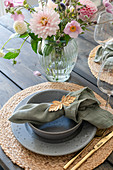 A place setting and a bouquet on a patio table