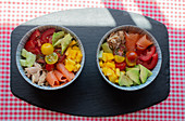 Top view of bowls with chopped fresh vegetables and meat of salmon and chicken placed on table in kitchen for lunch