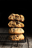 Stack of tasty cookies with chocolate placed on wooden table on black background