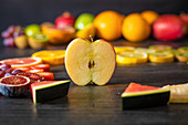 Various peeled and cut healthy fruits and vegetables arranged on a black lumber table