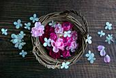 Rosa Rosenblüten im Korb auf rustikalem Holzuntergrund