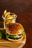Blue cheese and basil beef burger with mustard barbecue sauce and french fries