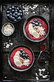 Raspberry smoothie bowl with blueberry banana and almond flakes