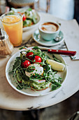 Avocado toasts with a poached egg with tomatoes and lettuce