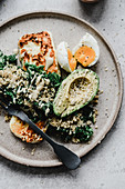 Millet with avocado kale egg and grilled halloumi topped with tahini sauce