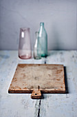 An arrangement of vintage bottles and a wooden board