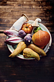 Fresh vegetables, mushrooms and pear on an enamel plate