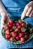 Frau hält Teller mit frischen Erdbeeren