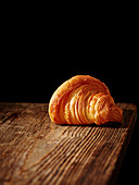 A croissant on a wooden board