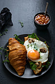 Croisant with fried egg, mushrooms, beans and grean leaves