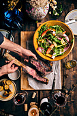 Carved tomahawk steak on a table laid with a mixed leaf salad and sweetcorn