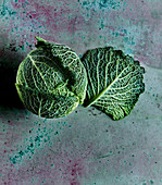 A Savoy cabbage on a green concrete surface
