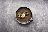 Green asparagus in vegetable consommé with a black tea broth and a sous vide egg