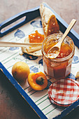 Delicious sweet apricot jam in glass pot served on tray with toast and fresh apricot