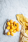 Fresh yellow ripe apricots placed on yellow cloth on white marble table