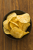 Knusprige Kartoffelchips in einem Schälchen (Aufsicht)
