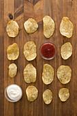 Knusprige Kartoffelchips aufgereiht mit Ketchup und Sauerrahm