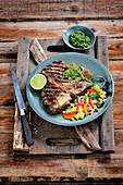 T-bone steak with chimichurri sauce and avocado corn salad