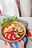 Insalata caprese made from red and yellow tomatoes