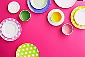 Buntes Geschirr auf pinkfarbenem Untergrund