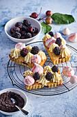 Kleine Pflaumen-Mohn-Kuchen mit Brombeeren und Baiser