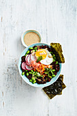 Warm Japanese rice salad bowl with edamame and fried egg