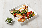 Grilled corn-fed chicken with halloumi, colourful tomato salad and pesto