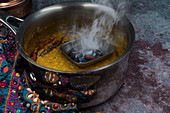 Tarka dhal – yellow lentil curry being made (India)