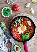 Shakshuka with eggs and quinoa placed on table with fresh ingredients