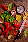 Chopping board with knife and chilli, basil, lime, garlic and salt