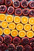 Angeschnittene Orangen und Granatäpfel in Reihen