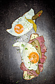 Grilled pastrami on bread with a fried egg and gherkins