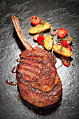 Grilled tomahawk steak with a potato and tomato ragout