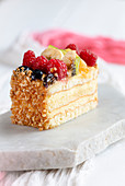 Classic vanilla and sponge fruit slice decorated with chopped nuts