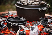 A Dutch oven placed directly on the coals