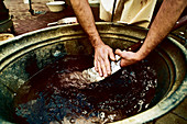 DIY slaughtering: a meat cleaver being cleaned in a vat of water