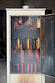 Various types of meat in a smoking oven