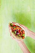 Hände halten Fajita mit Hähnchen und Tomaten