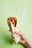 Hand hält Fajita mit Hähnchen und Tomaten
