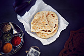 Naan bread on greaseproof paper and masala box