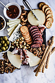 Cheese and salami board with crackers and olives