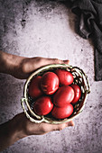 Hands holding basket with red eggs