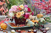 Herbststrauß aus Rosen, Hortensie, Fencheldolden, Hagebutten, Brombeeren und Herbstlaub, Kastanien, Kürbisse als Deko