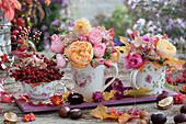 Kleine Sträuße aus Rosen, Hagebutten und Hortensie in Tassen, herbstlich dekoriert mit Kastanien, Strohblumenblüten und Herbstlaub